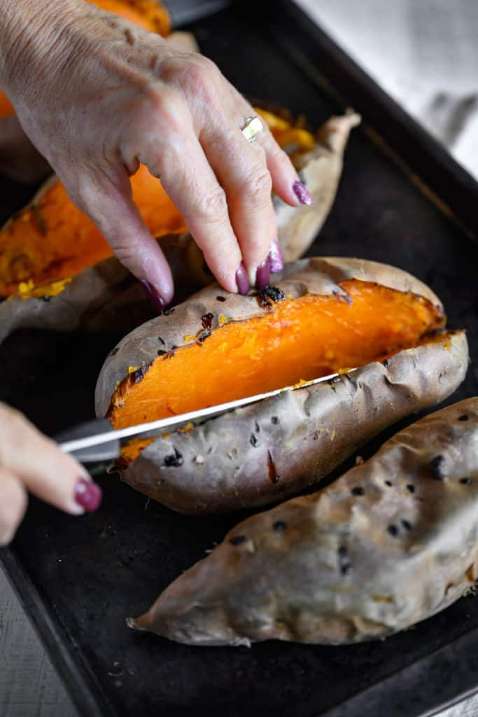 baked sweet potato being sliced lengthwise in half