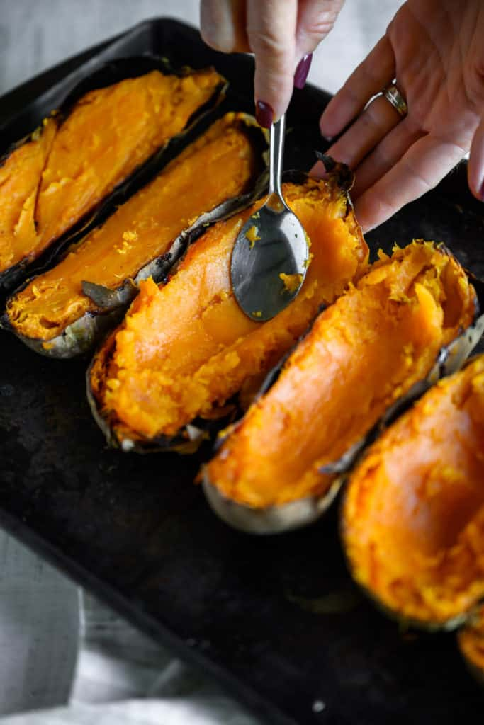 spoon makes a well in baked sweet potatoes