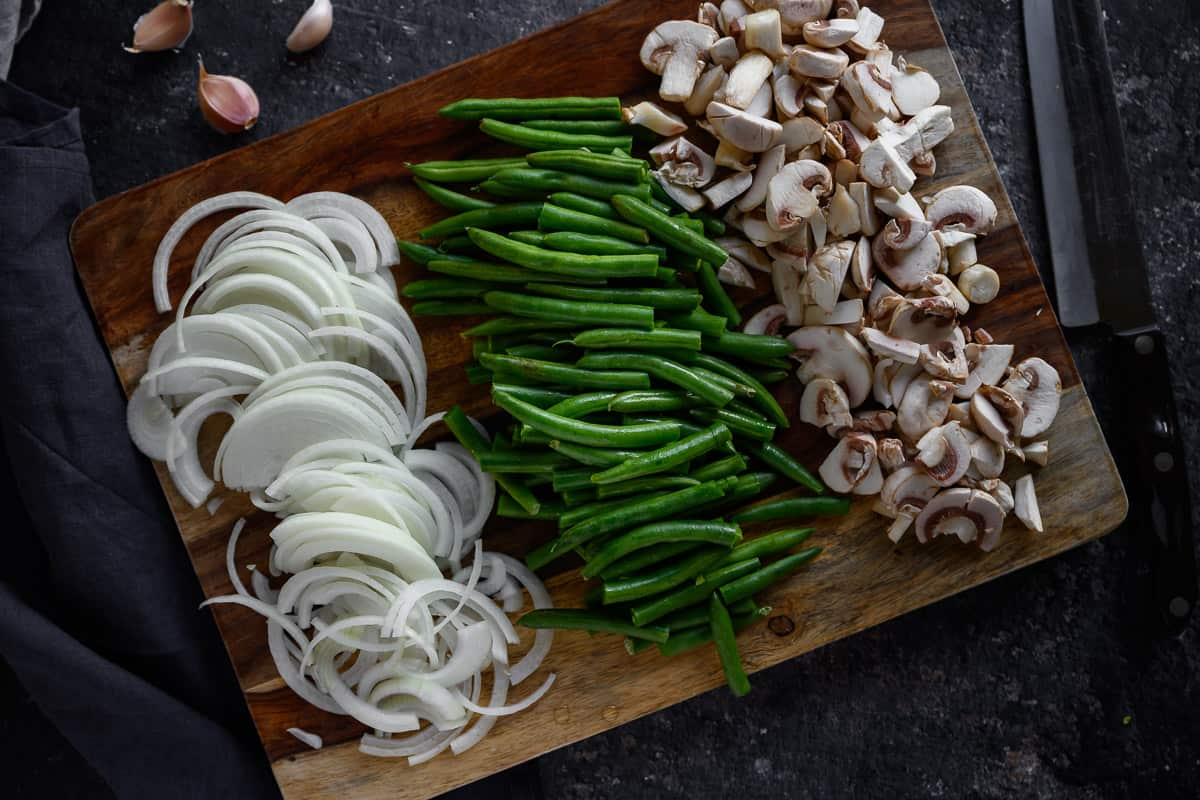 sliced onions, green beans, mushroom slices on a cutting board