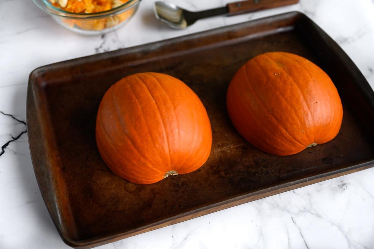 pie pumpkins cut side down on a rimmed baking sheet