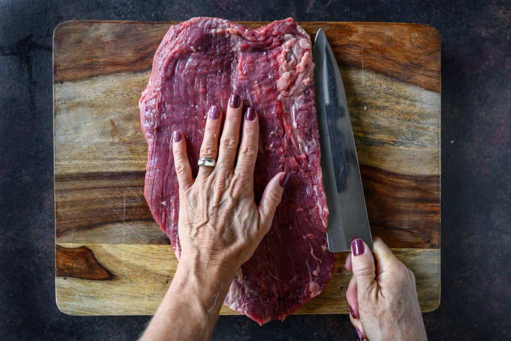 one hand holding steak secure while other hand cuts horizontally to butterfly the meat