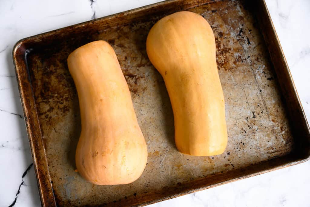 butternut squash cut in half lengthwise on a rimmed baking sheet skin side down