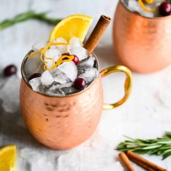 non-alcoholic cranberry moscow mule in a copper mug, garnished with orange peel, orange wedge, and cinnamon stick