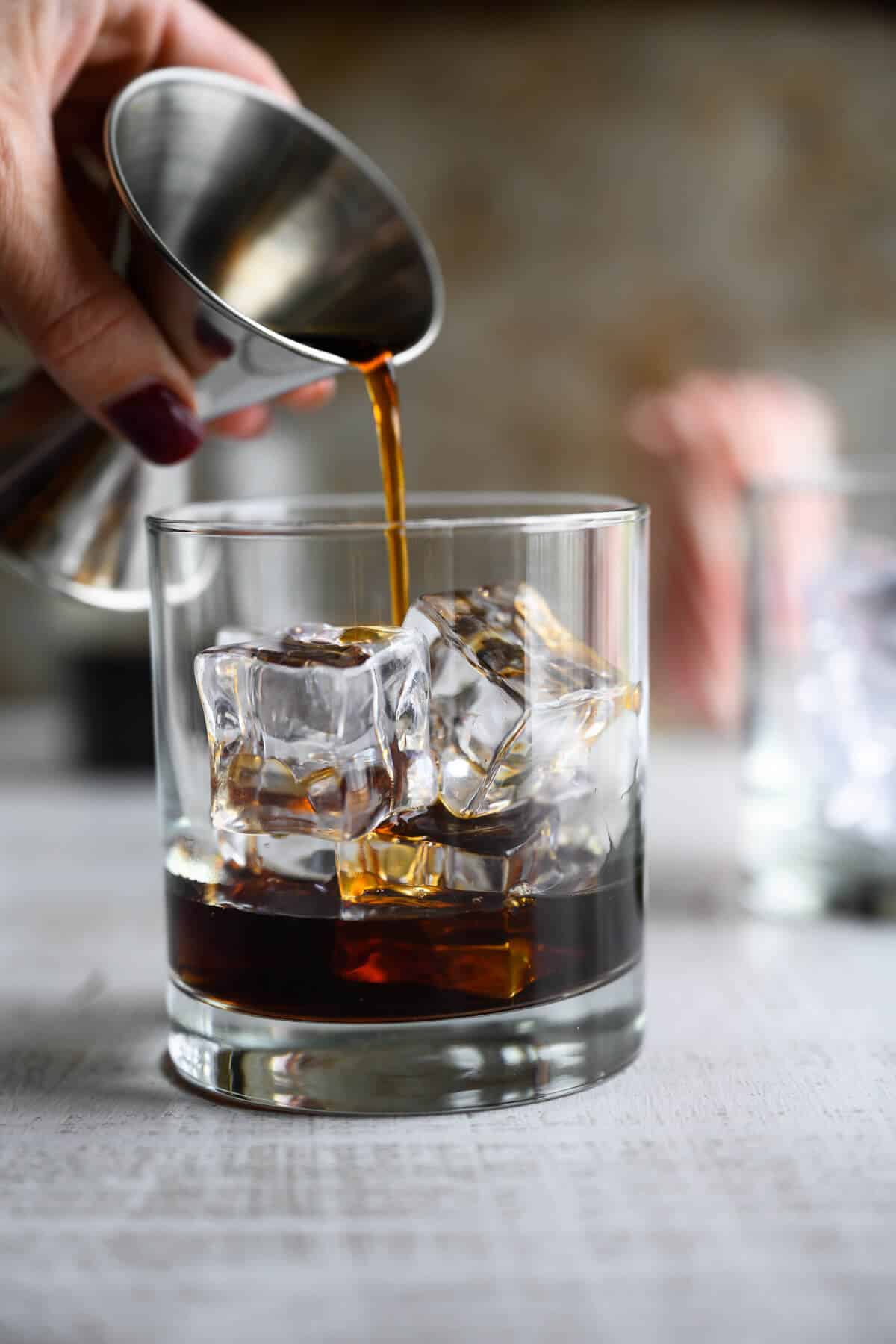 coffee being poured over ice from a jigger.