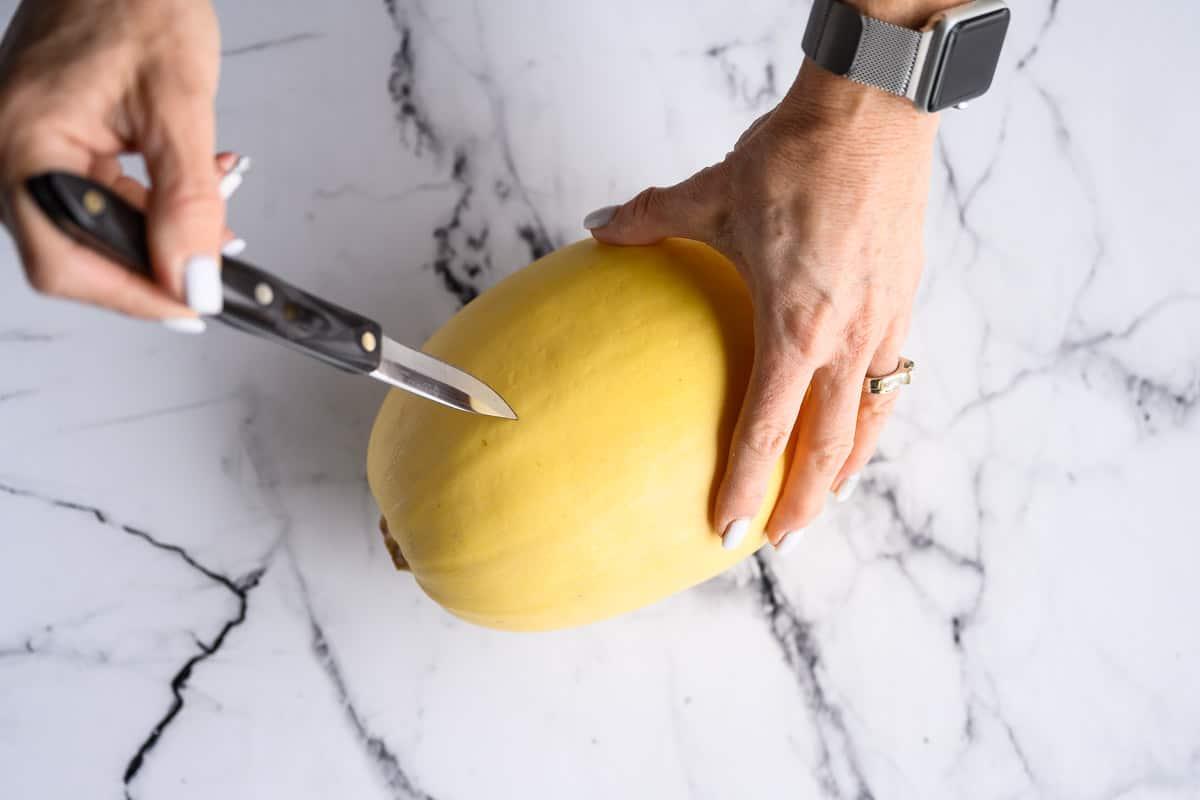 whole raw spaghetti squash being pierced by a pairing knife.