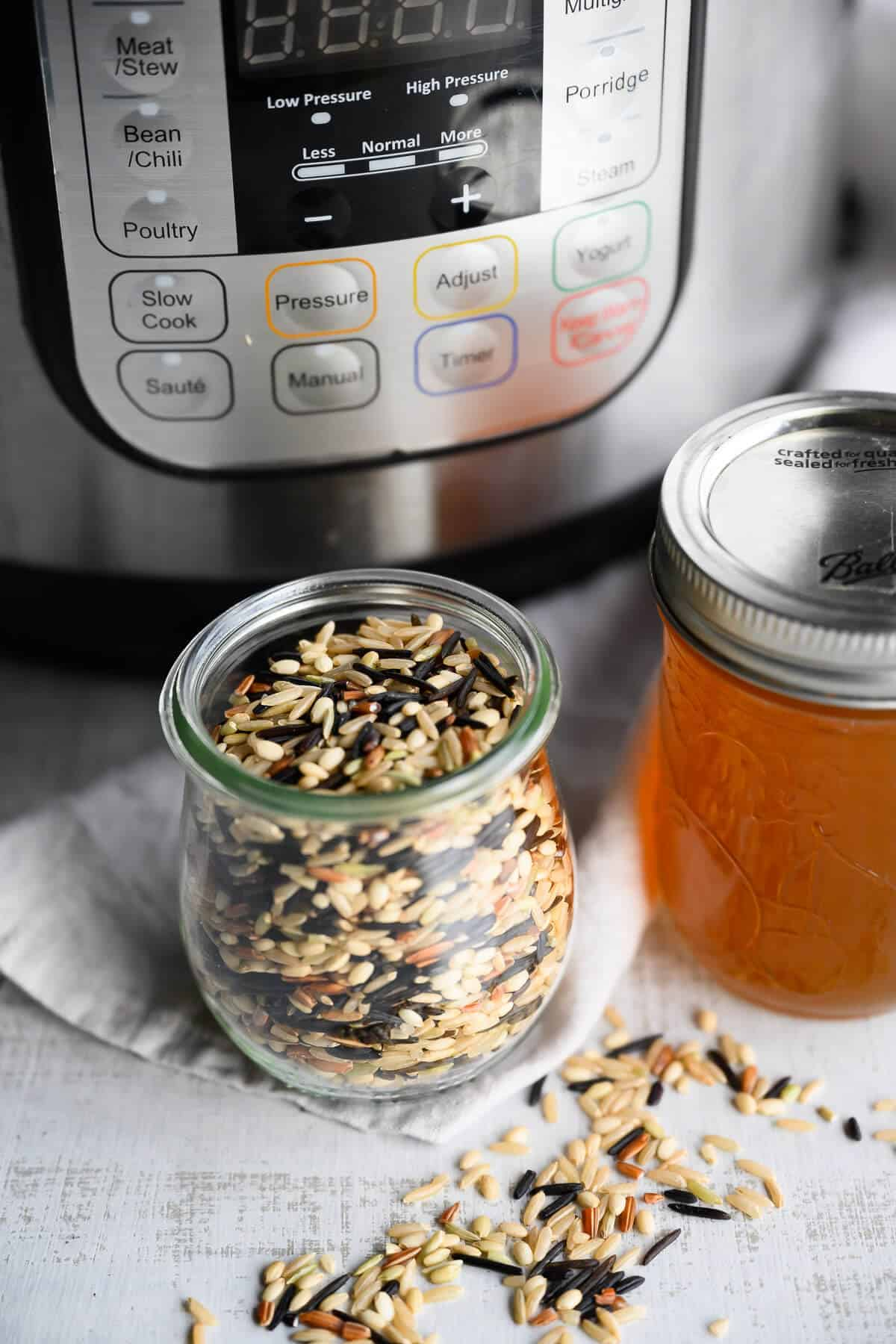 jar of uncooked dry wild rice next to vegetable broth and the instant pot