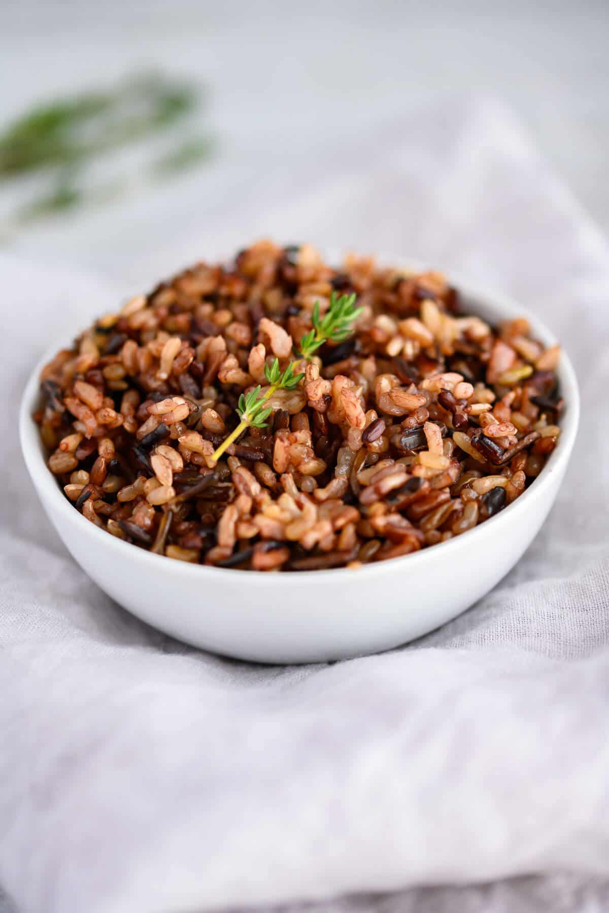 white bowl of cooked wild rice garnished with a sprig of thyme