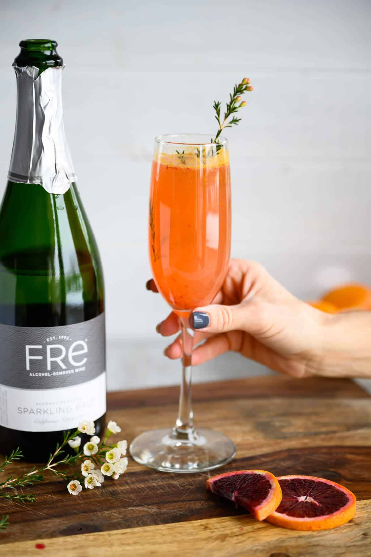 hand grabbing blood orange mimosa mocktail