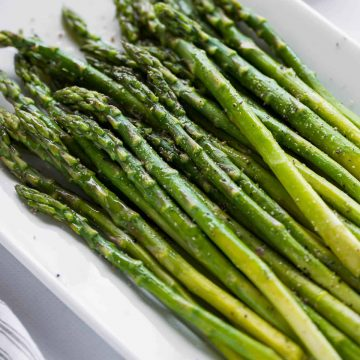 platter of asparagus garnished with oil and lemon