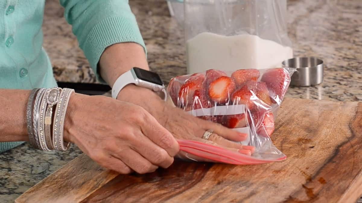 pressing air out of bag of strawberries