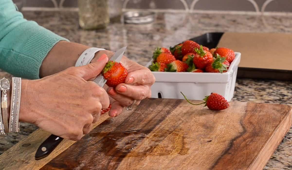 slicing strawberry stems off