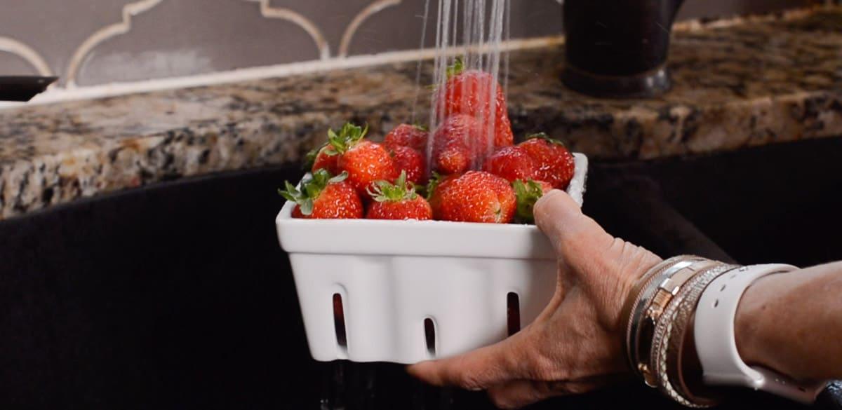 quart of fresh strawberries under running water