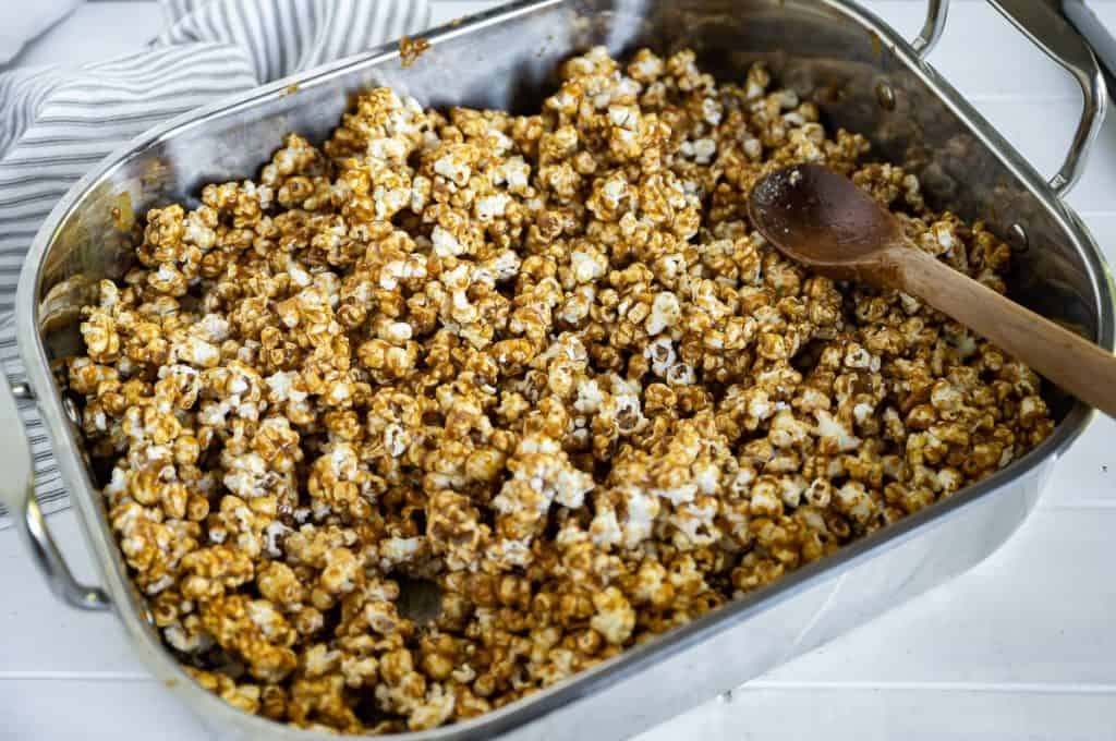 popcorn coated in caramel sauce in a roasting pan prior to cooking