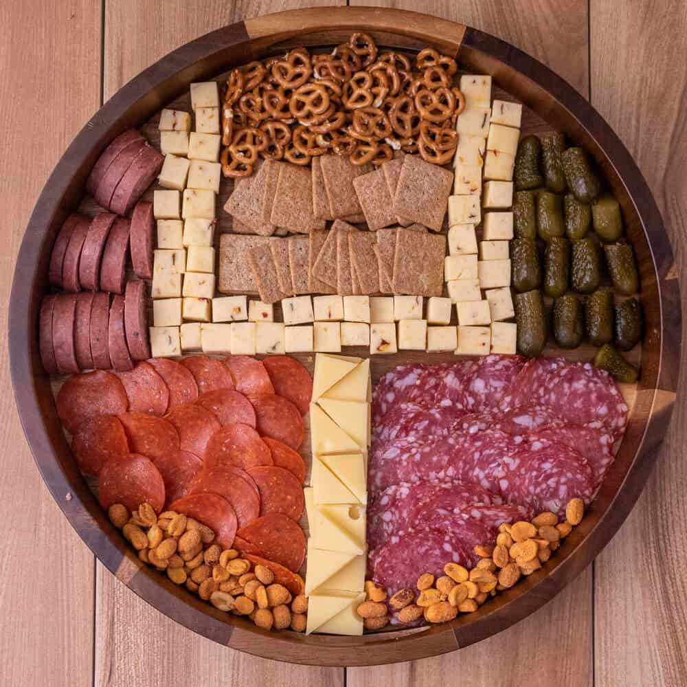 round charcuterie board where the meat, cheese, crackers and other elements represent a football field goal post