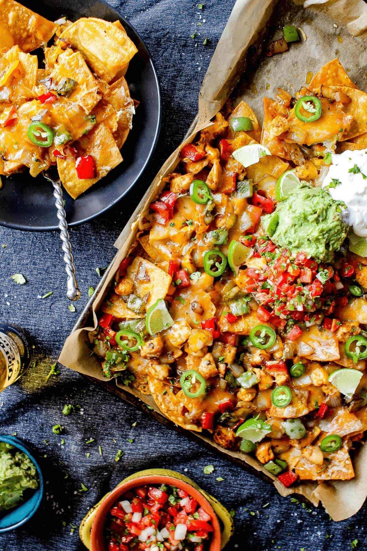 sheet pan full of chicken fajita nachos alongside garnishes of salsa, guacamole, and a plate full fo nachos