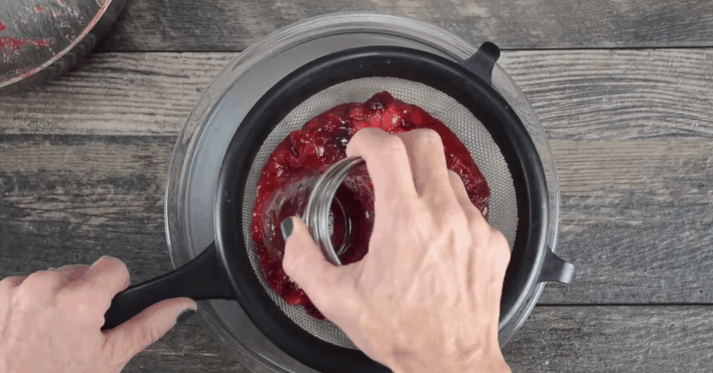 straining homemade cranberry sauce with a fine mesh sieve and a mason jar