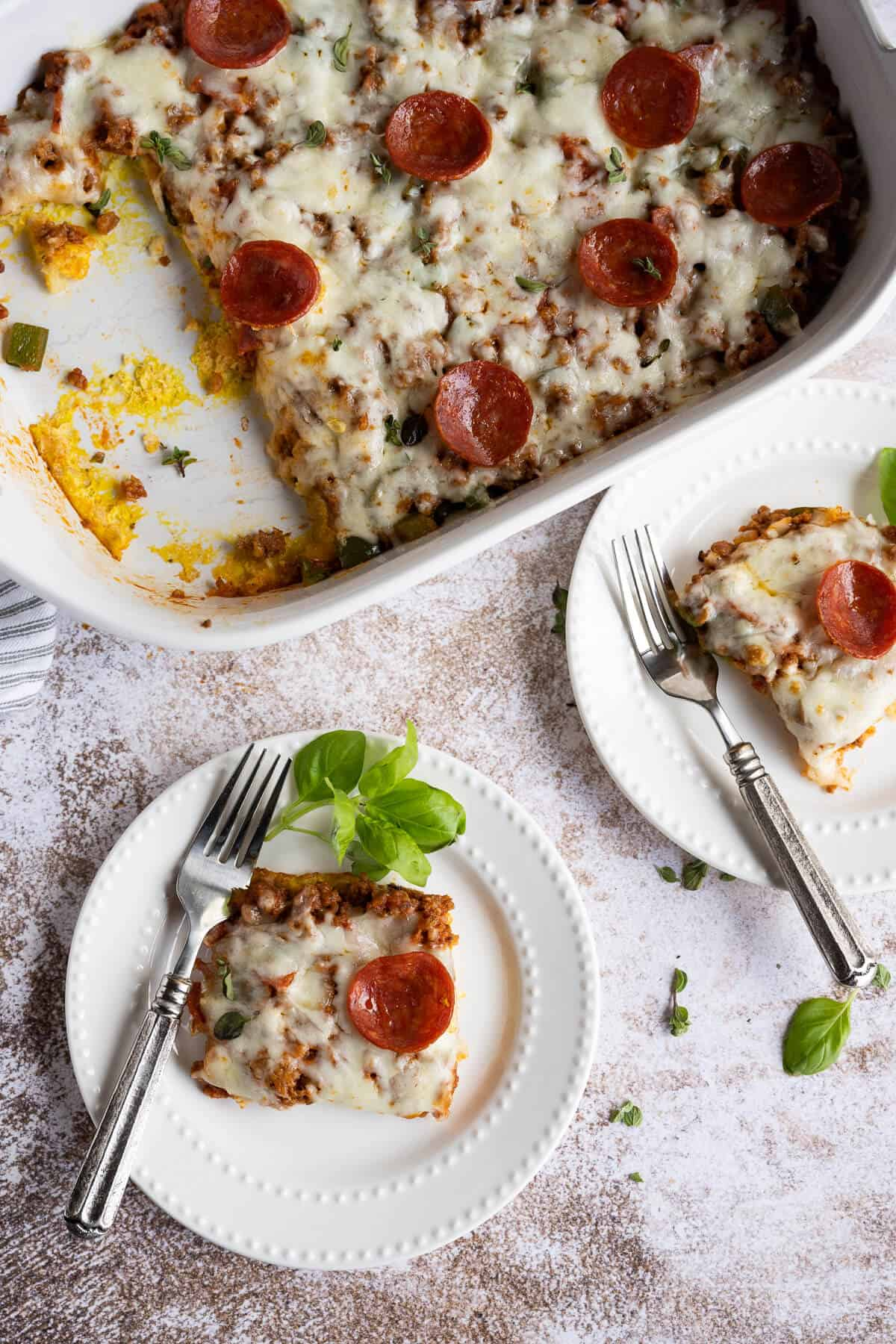 two plates with pieces of low carb pizza casserole garnished with fresh basil