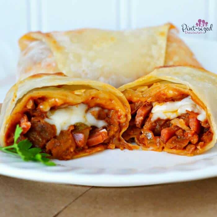 homemade pizza eggroll split in half to show the pepperoni and cheese on the inside.