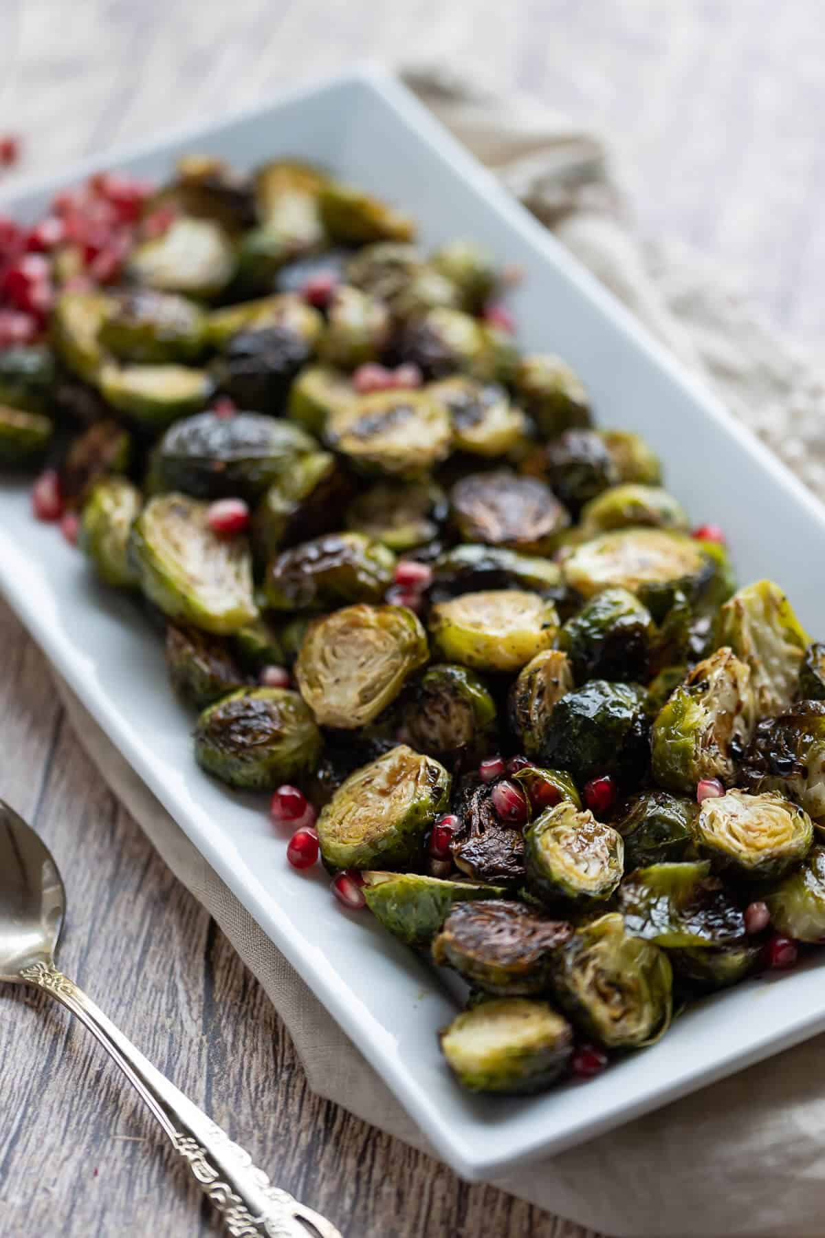 platter of roasted brussels sprouts garnished with pomegranate seeds