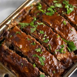 sliced low carb meatloaf in a loaf pan that has been glazed with sauce and garnished with parsley
