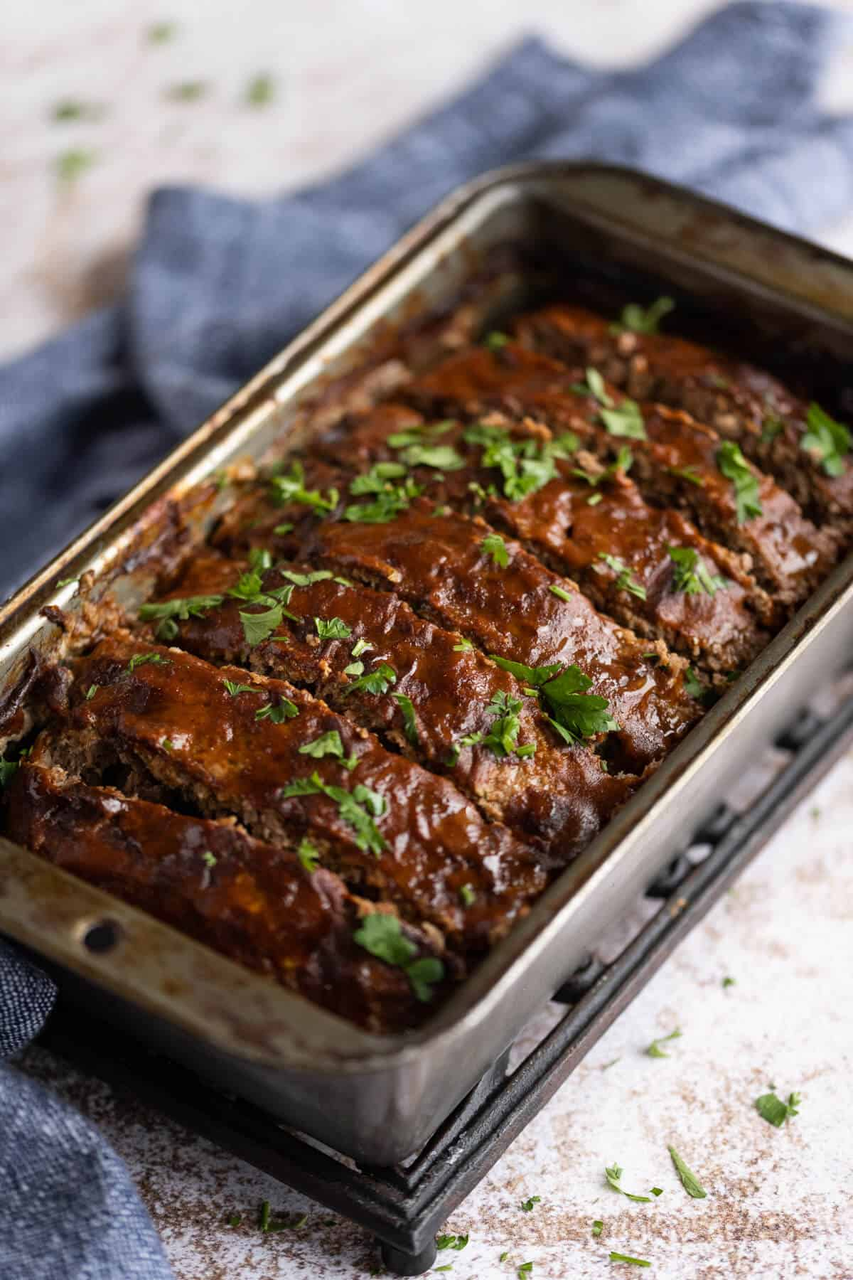 cooked meatloaf in a loaf pan that has been glazed with bbq sauce and garnished with fresh parsley