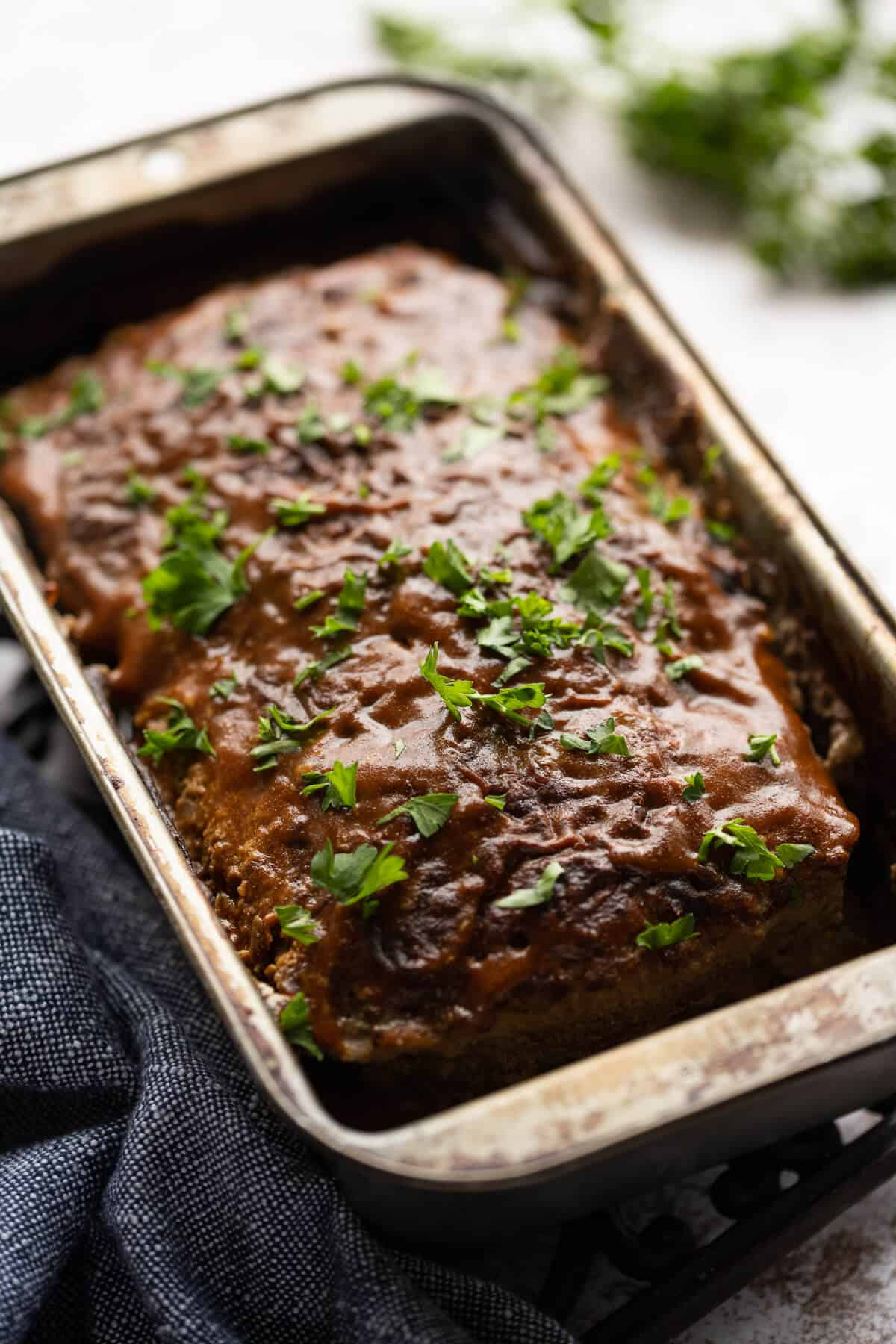 cooked meatloaf glazed with bbq sauce and garnished with parsley in a loaf pan