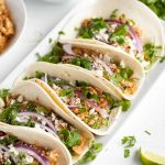 platter of soft tacos with chicken tinga, red onion, cheese, and cilantro