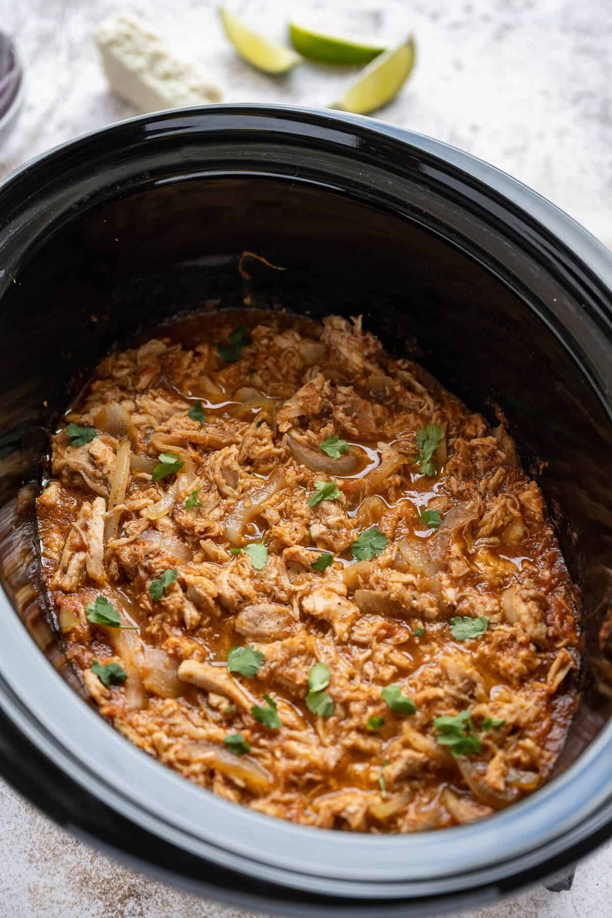 cooked chicken tinga simmering in sauce in a crockpot garnished with cilantro