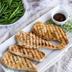 grilled chicken with teriyaki sauce on a white platter, served with green beans and white rice