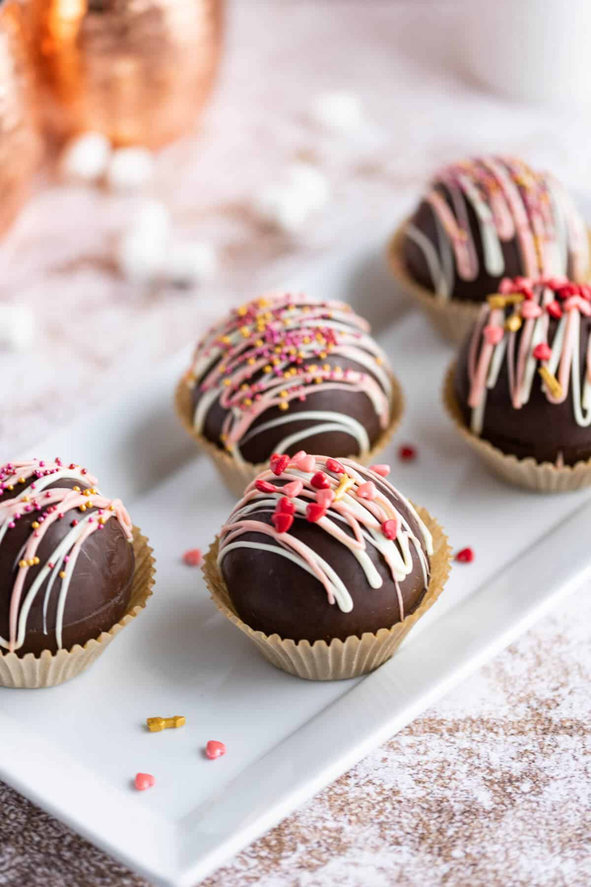 a platter of hot chocolate bombs decorated with pink and white chocolate drizzle and valentine sprinkles