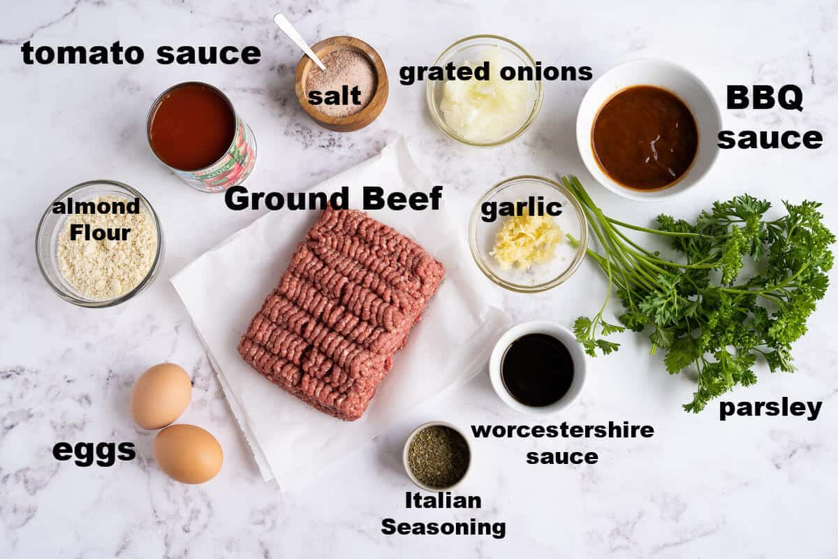 ingredients for low carb meatloaf: ground beef, tomato sauce, onions, almond flour, garlic, Italian seasoning, worcestershire sauce, bbq sauce, eggs, and parsley