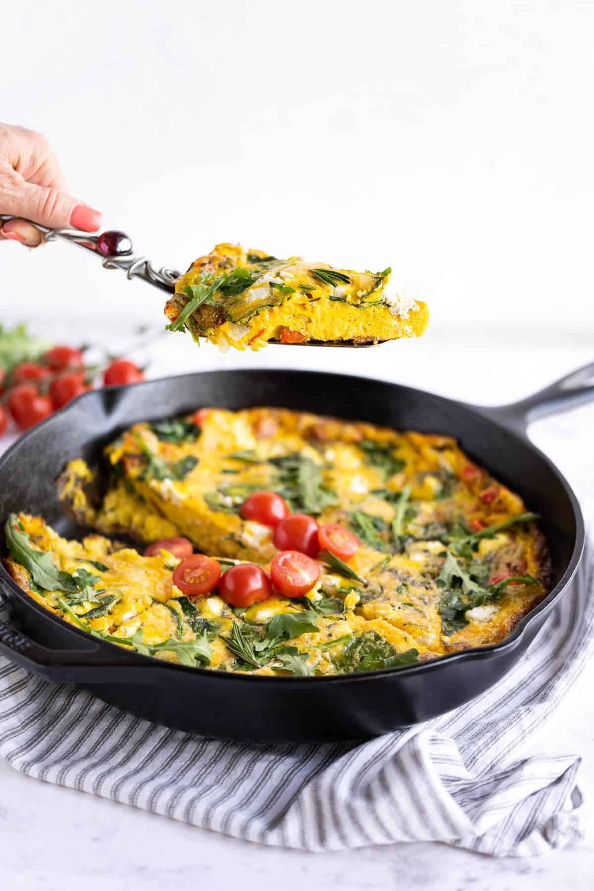 slice of frittata on a spatula being held above the whole frittata in a cast iron pan
