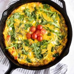 cooked frittata in a cast iron pan garnished with arugula, rosemary, and diced tomatoes