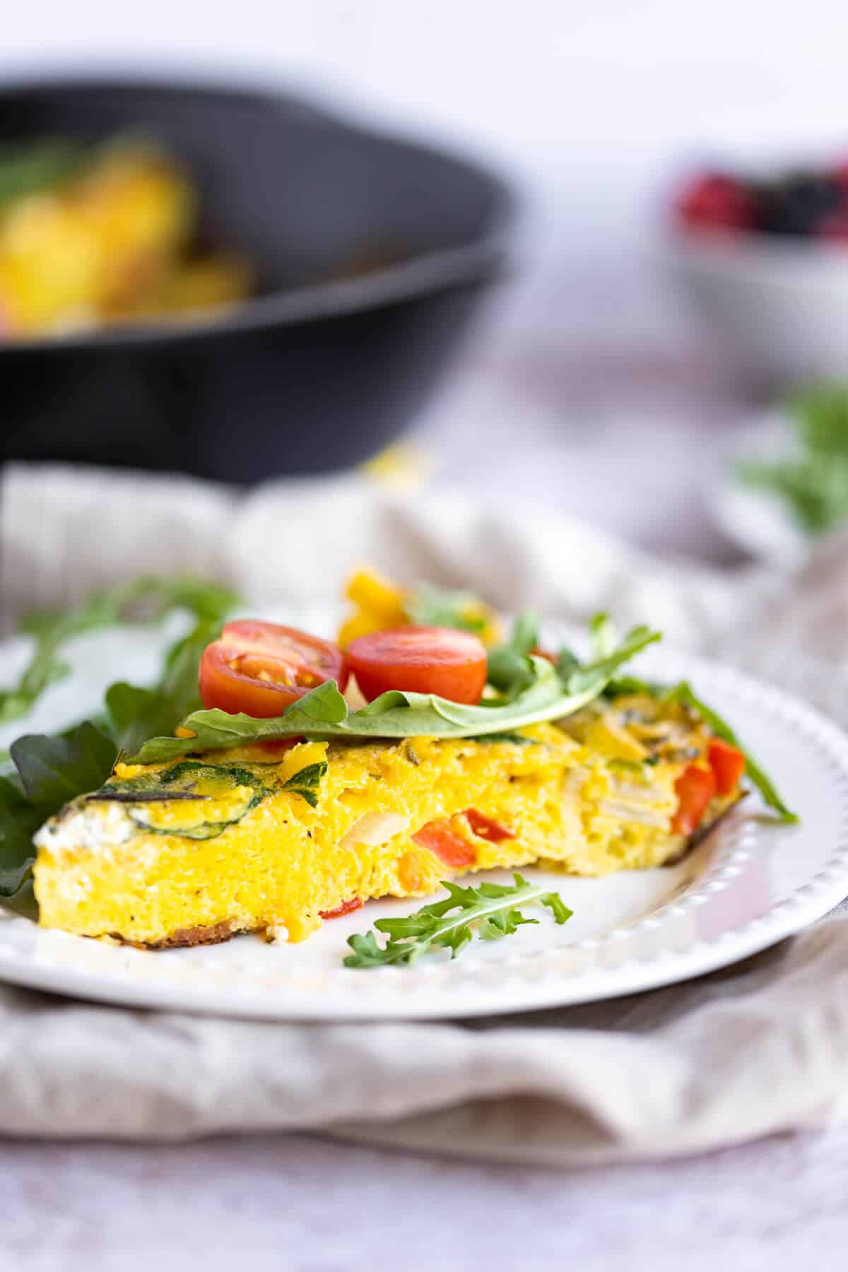 side view of a fluffy egg frittata topped with arugula and tomatoes