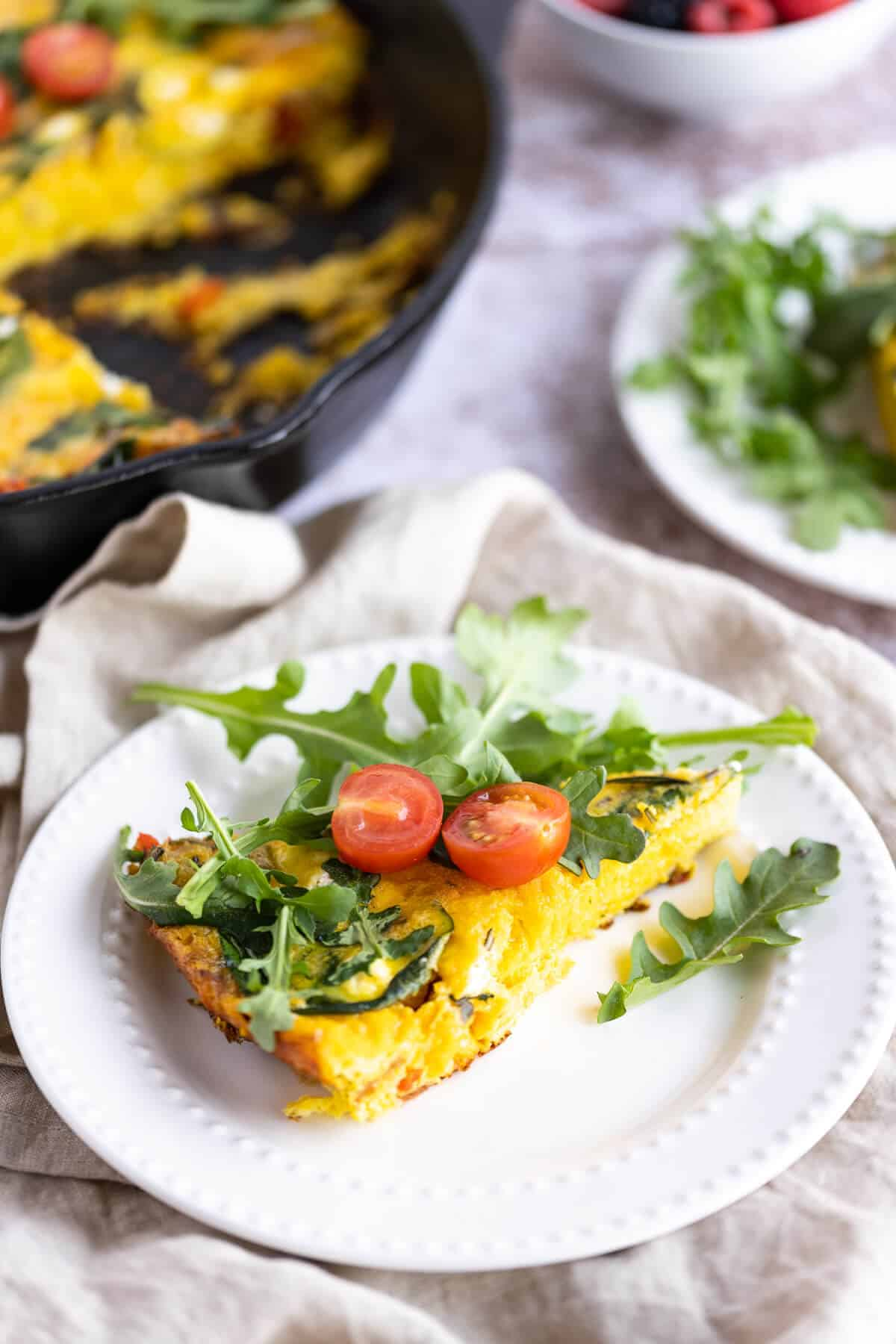 slice of a frittata on a white plate garnished with arugula