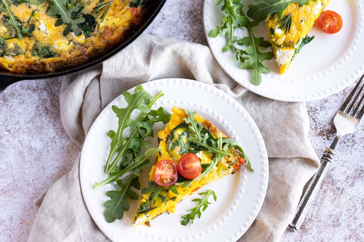 2 white plates with a slice of fluffy egg frittata on each garnished with arugula and tomatoes