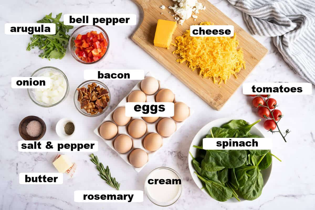 ingredients for a frittata: eggs, cream, bacon, onion, bell pepper, salt, pepper, butter, spinach, tomatoes, cheese, rosemary, arugula