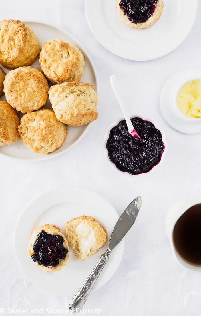 a plate full of round scones along side a plate with a single Irish scone topped with butter and jam