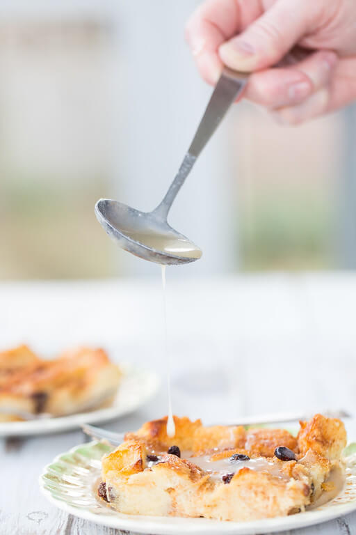 spoon pouring sauce over a piece Irish bread pudding