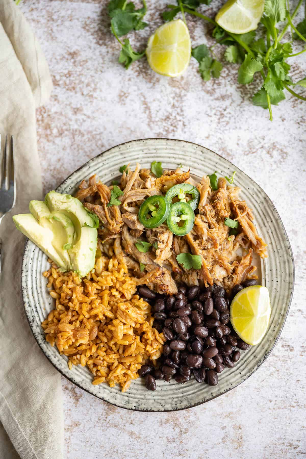 plate of carnitas with rice, beans, avocado and jalapeno