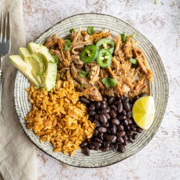plate of homemade pork carnitas served with rice and beans