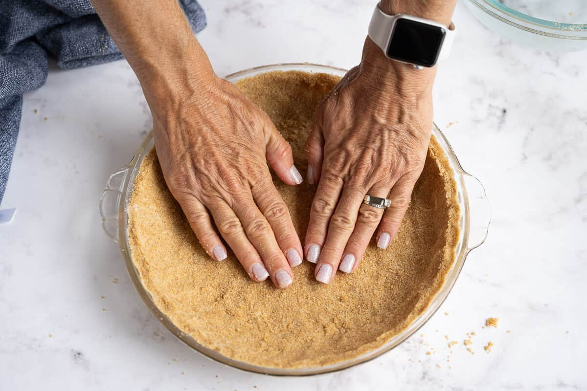 graham cracker crumb crust being pressed into a pie plate