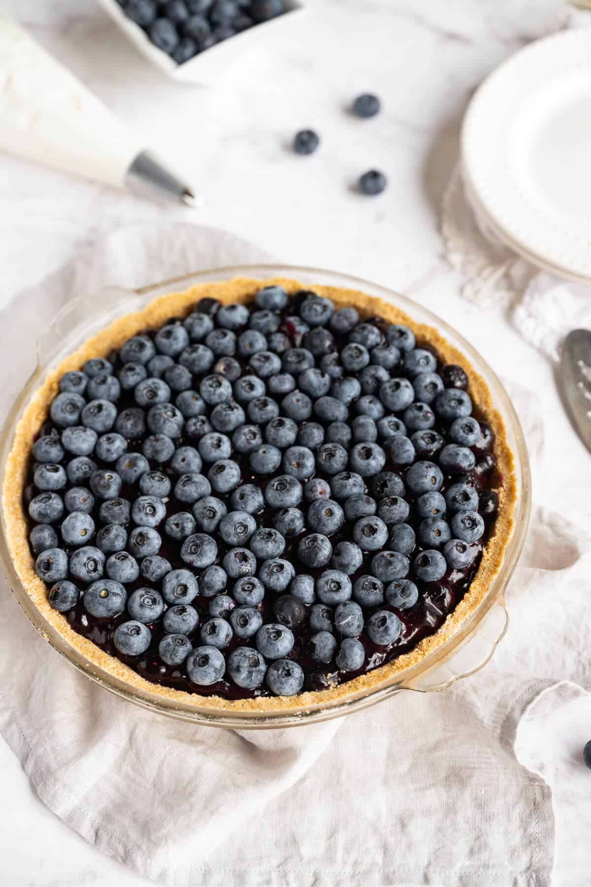 completed fresh blueberry pie next to plates and pie server