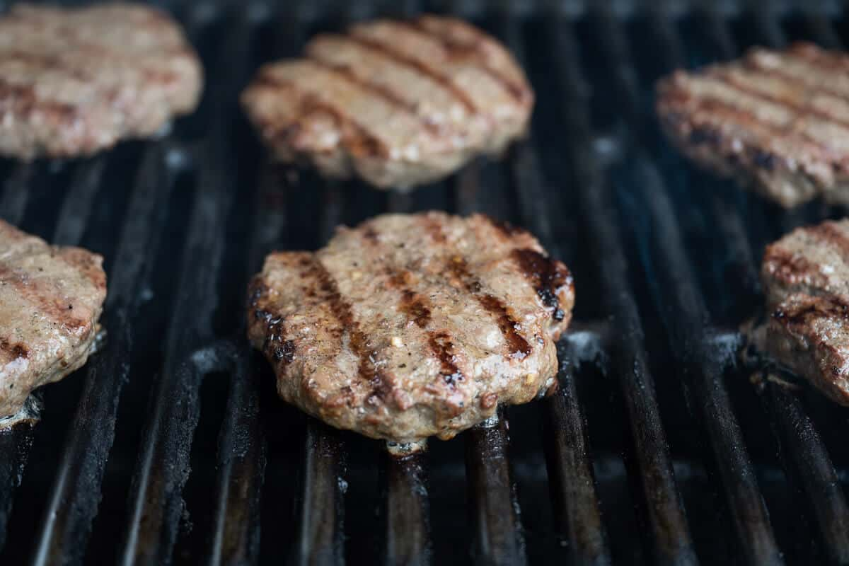 6 juicy burgers on the grill, showing grill marks