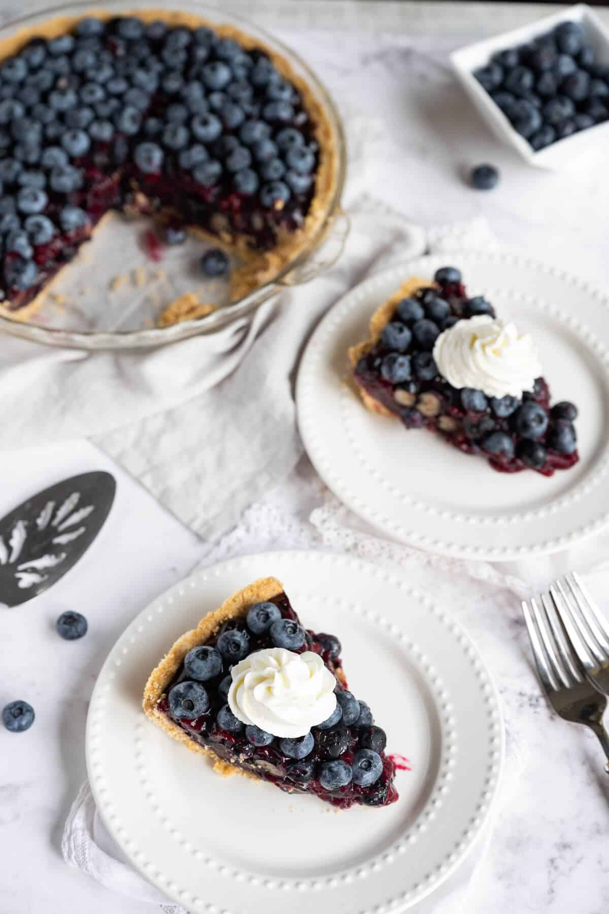 two slices of blueberry pie plated next to whole pie