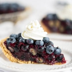 blueberry pie with graham cracker crust on a white plate topped with whipped cream