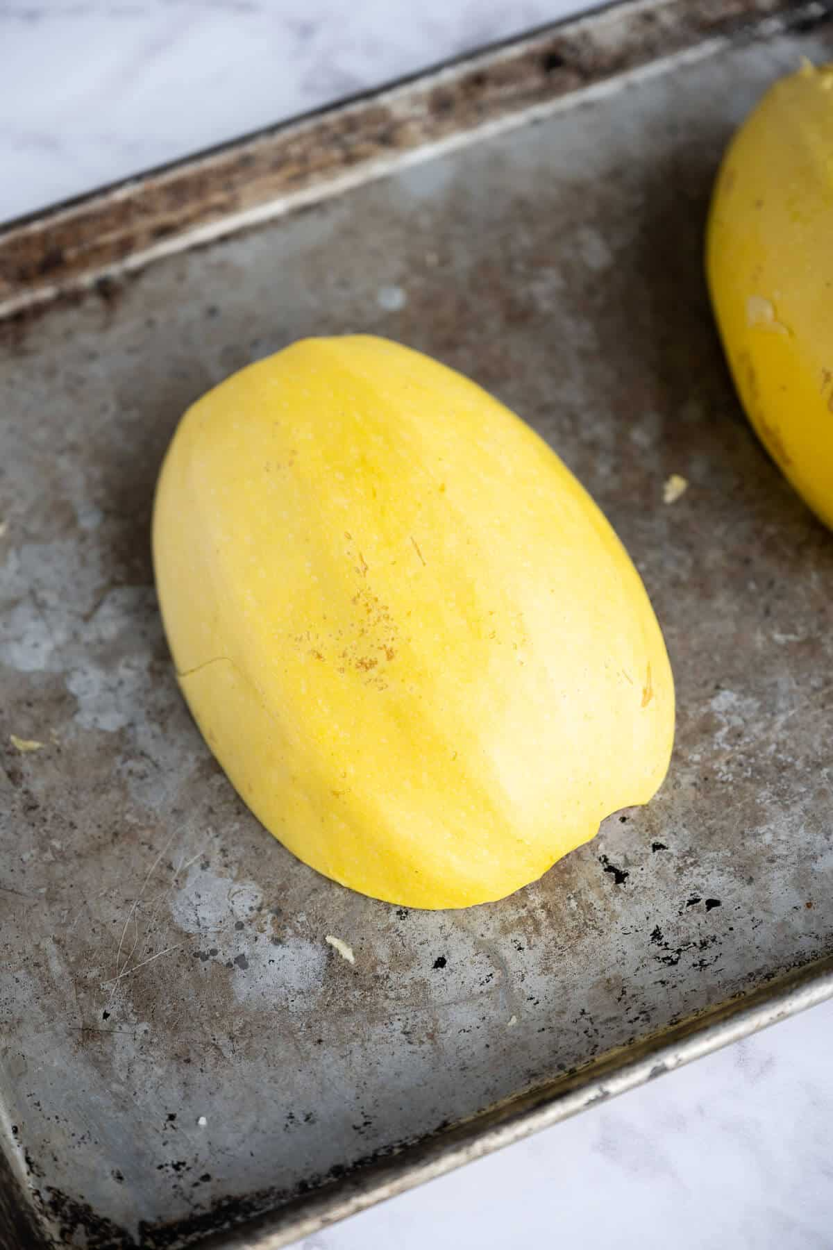 spaghetti squash sliced in half lengthwise cut side down on rimmed baking sheet.