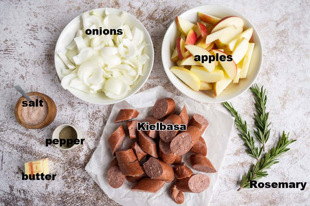 Ingredients for Kielbasa skillet dinner: onions, apples, kielbasa, salt, pepper, butter, and fresh rosemary.